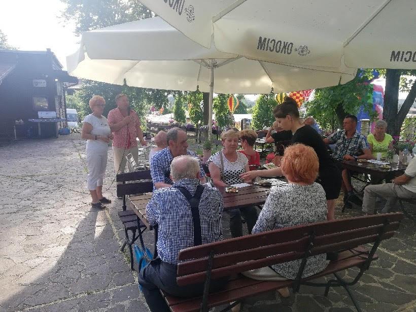 seniorzy rozmawiający i siedzący przy stole